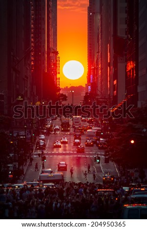 MANHATTAN, NY, USA - JULY 11, 2014 Manhattanhenge - Manhattanhenge phenomenon observed on 42nd street by people trying to photograph the sun setting between the high-rise buildings of the city. - stock photo