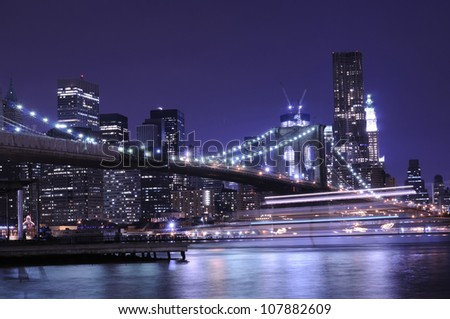 Manhattan skyline and Brooklyn bridge at night - stock photo