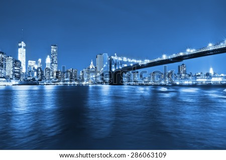 Manhattan skyline and Brooklyn Bridge at night. - stock photo