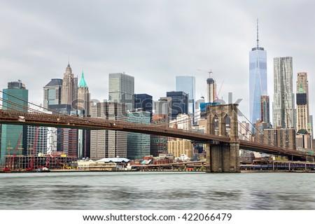 Manhattan skyline and Brooklyn Bridge on a cloudy day - stock photo