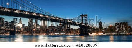 Manhattan Skyline and Manhattan Bridge At Night. Manhattan Bridge is a suspension bridge that crosses the East River in New York City.