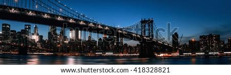 Manhattan skyline and Manhattan bridge silhouette at night. Manhattan bridge is a suspension bridge that crosses the East River in New York City.  - stock photo