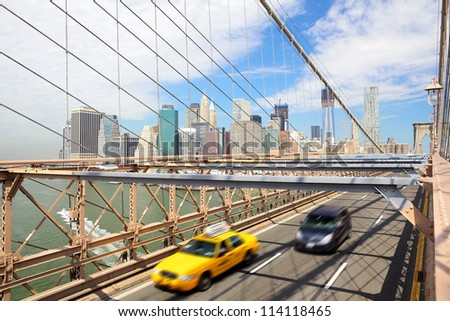 Manhattan skyline and taxi cab crossing Brooklyn Bridge, New York - stock photo