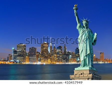 Manhattan skyline at night and Statue of Liberty. - stock photo