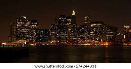 Manhattan skyline over the bay at night - stock photo