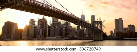 Manhattan skyline panorama and Brooklyn Bridge at sunset, New York City - stock photo