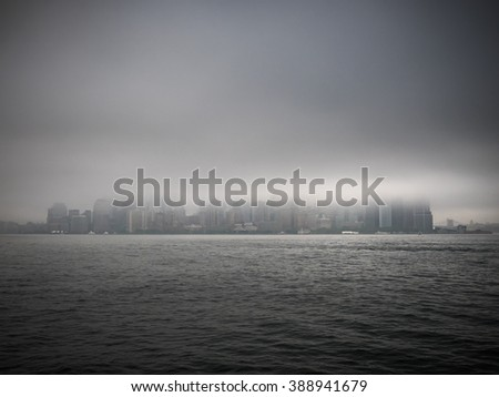 manhattan skyline seen from the harbor during foggy, gray weather - stock photo