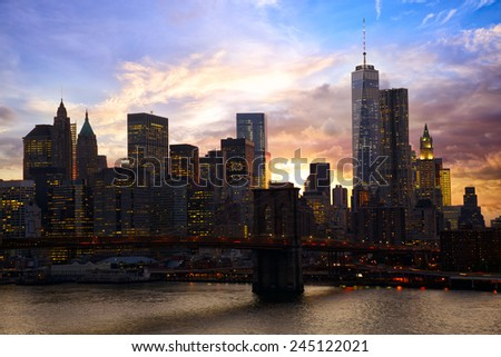 Manhattan skyline with Brooklyn Bridge at sunset, New York - stock photo