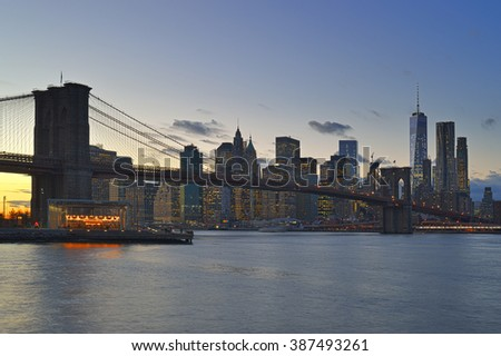 Manhattan skyline with Brooklyn Bridge at twilight. - stock photo