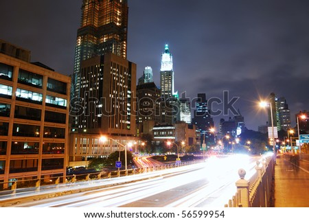 Manhattan street view at night in New York City with light beams of traffic on road. - stock photo