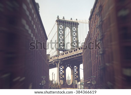 Manhattan Suspension Bridge as seen from Street Level Between Low Rise Apartment Buildings with Traditional Architecture and View of New York City Skyscrapers in Background, New York, USA - stock photo