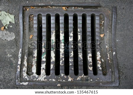 Manhole cover metal storm drain with warnings - stock photo