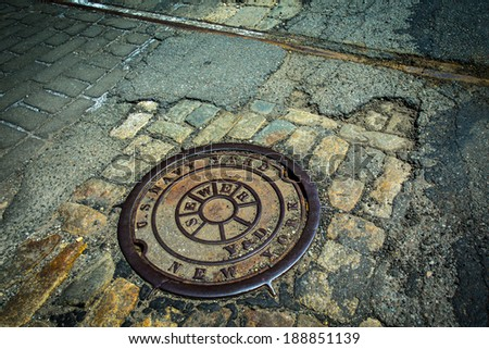 Manhole drain cover on rough old cobblestone and asphalt street at historic Brooklyn Navy Yard - stock photo