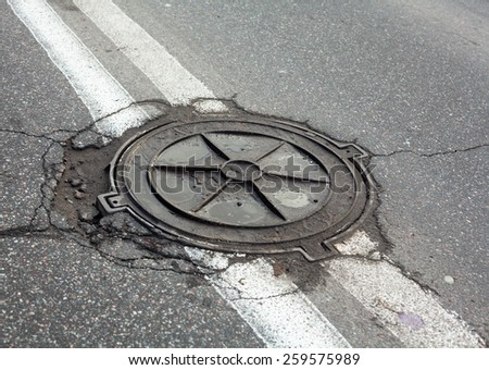 Manhole on the road within the double solid white center-lines of the road marking