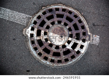 Manhole with metal cover in asphalt with white road marking line on it. - stock photo