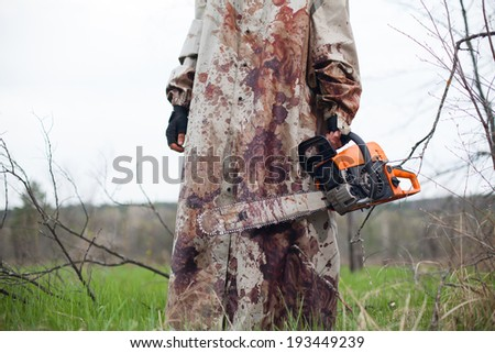 Maniac with the chainsaw dressed in a dirty bloody raincoat.  - stock photo