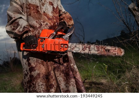 Maniac with the chainsaw dressed in a dirty bloody raincoat. Sunset forest on the background - stock photo