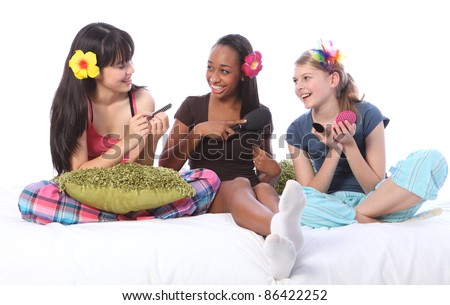 Manicure and make up game fun at pyjama party for three happy teenage girl friends, a mixed race african american, oriental Japanese and blonde caucasian school mates. - stock photo