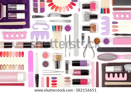 manicure and pedicure tools and other essentials on white background top view. flat lay composition in pink and violet colors - stock photo