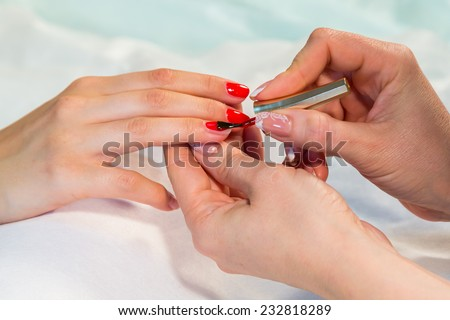 Manicure. applying red nail polish. Closeup of Woman applying nail varnish to finger nails.Manicure process.Beautiful manicure process. Nail polish being applied to hand, polish in red color