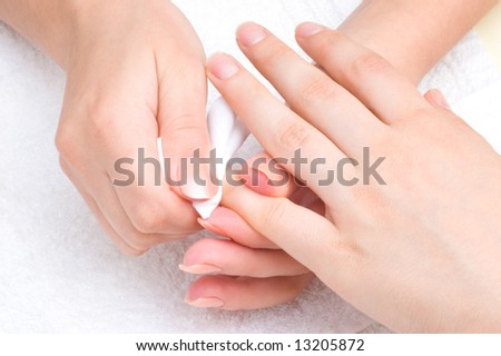manicure applying - wiping the moisturizer from end of fingers