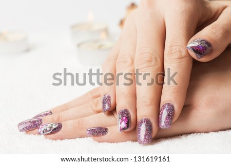 Manicure - Beautiful manicured woman's nails with glitter purple gel nail polish on soft white towel. Selective focus. - stock photo