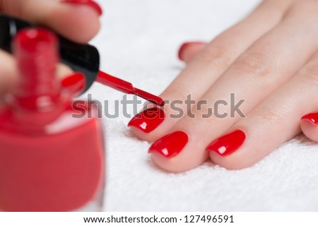 Manicure - Beautiful manicured woman's nails with red nail polish on soft white towel. - stock photo