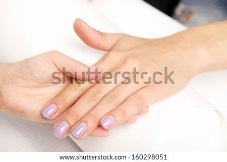 Manicure - Beautiful manicured woman's nails with violet nail polish on soft white towel.