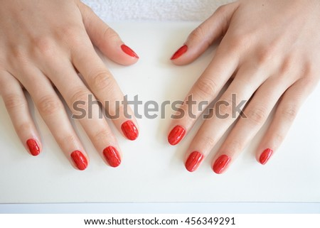 manicure. beautiful red manicure in beauty salon. beautiful manicured hand with red nails on white background