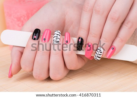 Manicure - Beautifully manicured woman fingernails. Feminine nail art with interesting animal print nail art. Selective focus. - stock photo