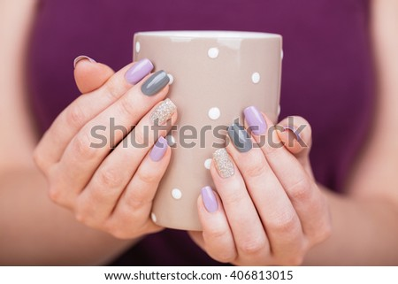 Manicure - Beauty photo of nice manicured woman fingernails holding a cup. Very nice feminine nail art with nice purple,silver and grayish nail polish. Processed in retro colors. Selective focus. - stock photo