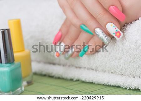 Manicure - Beauty treatment photo of nice feminine manicured woman fingernails holding nail file. Selective focus. - stock photo