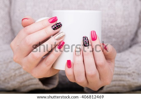 Manicure - Beauty treatment photo of nice manicured woman fingernails holding a cup. Very nice feminine nail art with nice pink,black and gold nail polish. Processed in retro colors. Selective focus. - stock photo