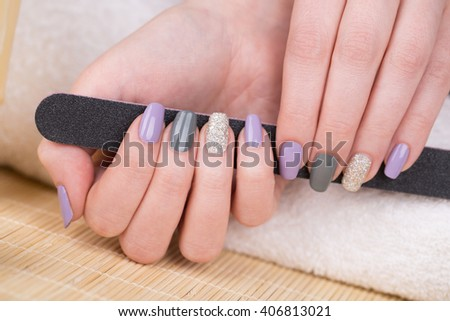 Manicure - Beauty treatment photo of nice manicured woman fingernails holding a nail file. Very nice feminine nail art with nice purple,silver and grayish nail polish. Selective focus. - stock photo
