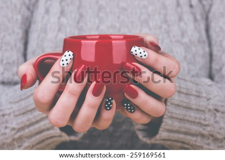 Manicure - Beauty treatment photo of nice manicured woman fingernails. Very nice feminine nail art with nice red, white and black nail polish. Processed in retro colors. Selective focus. - stock photo
