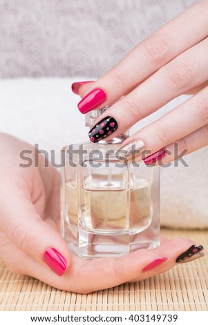Manicure - Beauty treatment photo of nice manicured woman fingernails. Very nice feminine nail art with nice pink, gold and black nail polish. Focus is on black nail. - stock photo