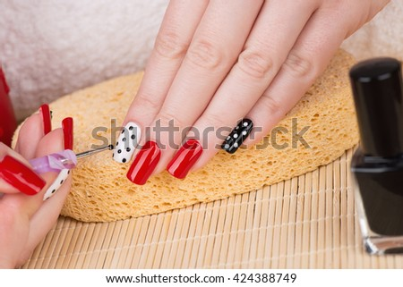 Manicure - Beauty treatment photo of nice manicured woman fingernails. Very nice feminine nail art with nice red, white and black nail polish. - stock photo