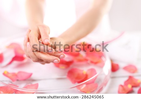 Manicure, hands ready for summer.. Beauty ritual for hands. Care treatment of hands and nails woman hands over the bowl with rose petals  - stock photo