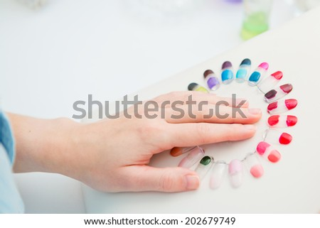 Manicure in process. Woman selects colors shellac - stock photo