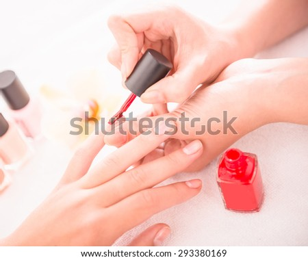 Manicure in the beauty salon. Drawing of red nail polish. Spa treatment. - stock photo