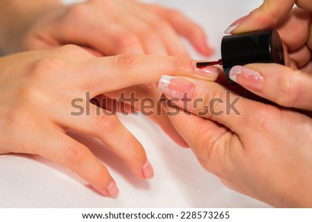 Manicure in the spa salon. Drawing of red nail polish. Spa manicure, nail care. Girl does a manicure. The concept of hand care.