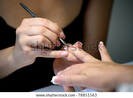 Manicure making female hands covering of pink enamel, macro - stock photo