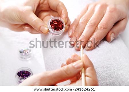 Manicure, nail decorating. Beauty salon, manicure, a woman at the beautician - stock photo