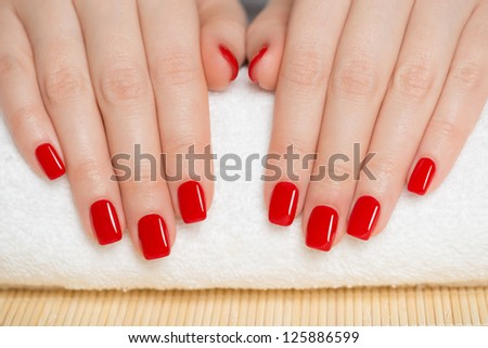 Manicure - nice manicured woman nails with red nail polish - stock photo