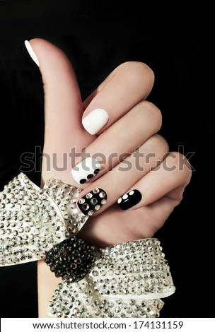 Manicure on short nails covered with black and white lacquered with rhinestones on a black background . - stock photo