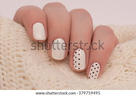 Manicure on short nails covered with black and white lacquered with rhinestones on a black background. Light manicure in light on a white background. - stock photo