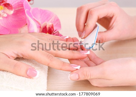 Manicure process in beauty salon close up - stock photo