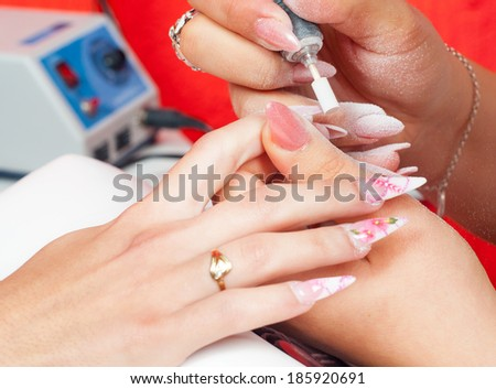 Manicure process in beauty salon showing filing and polishing of nails. - stock photo