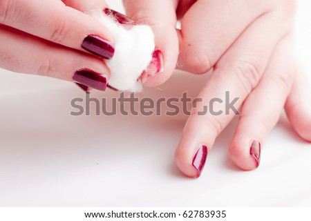 manicure process: removing nail polish with nail-polish remover and cotton wool - stock photo