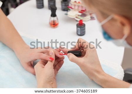 Manicure specialist painting clients nails red at the nail salon - stock photo